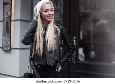 Portrait of beautiful young blonde woman wearing stylish black outfit, she smiling on urban background, happy time, Travel Concept.trendy girl in stylish sunglasses ad leather jacket in the street.