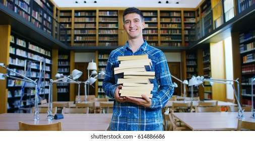 Portrait of a beautiful young boy smiling happy in a library holding books after doing a search and after studying. Concept: educational, portrait, library, and studious.