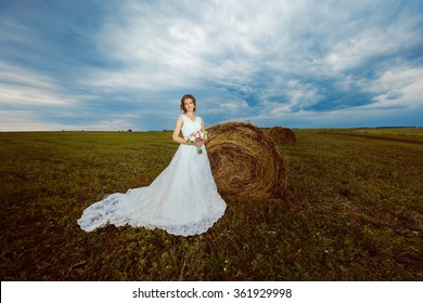 Portrait of beautiful young bride in gorgeous white dress at summer field with golden haystacks background.