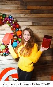 Portrait of a beautiful young brown-haired woman near a Christmas Balls. Christmas background