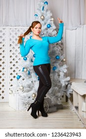 Portrait of a beautiful young brown-haired woman near a Christmas tree. Christmas background