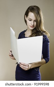 Portrait of beautiful young brunette with blank white folder.