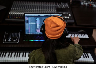 Portrait of beautiful young brunette, female artist playing keyboard synthesizer, sitting in recording studio