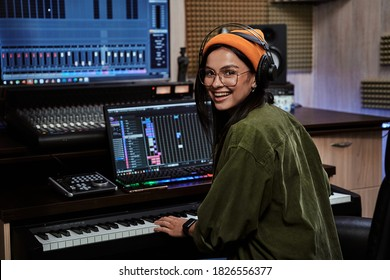 Portrait of beautiful young brunette, female artist smiling at camera while playing keyboard synthesizer, sitting in recording studio