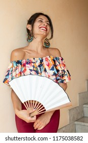Portrait of a beautiful young brunette holding a fan