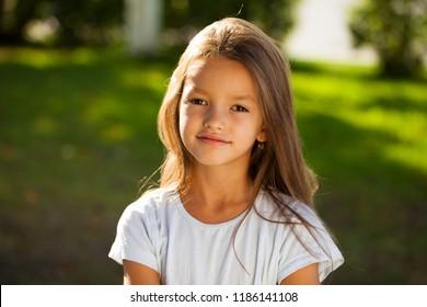Portrait of a beautiful young brunette little girl, summer outdoors