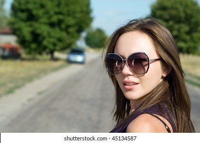 Portrait of beautiful young brunette on the road