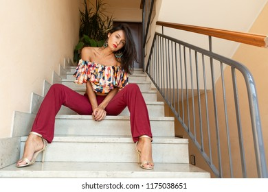 Portrait of a beautiful young brunette posing on the stairs