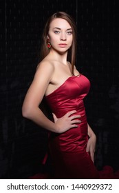 Portrait of a beautiful young brunette posing in the studio dressed in a luxurious evening red dress