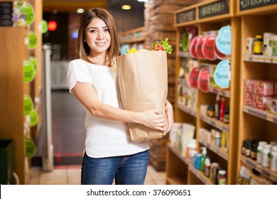 Portrait of a beautiful young brunette standing in one of the aisles of a supermarket while carrying a shopping bag