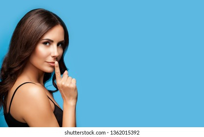 Portrait of beautiful young brunette woman with finger on lips, on blue background, with big copy space area, for some text, advertising or slogan