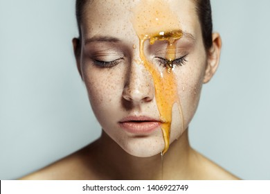 Portrait of beautiful young brunette woman with freckles and honey on face with closed eyes and serious face. indoor studio shot isolated on gray background.