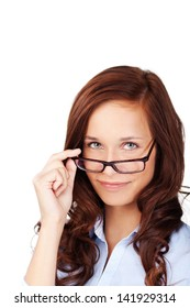 Portrait of a beautiful young brunette woman peering over the top her glasses at the camera isolated on white