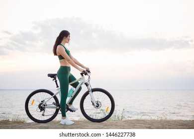 Portrait of a beautiful young brunette woman resting after bicycle ride at sunrise. Model listening to music with wireless earbuds in the morning.