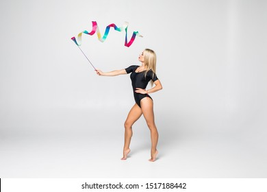 The portrait of beautiful young brunette woman gymnast training calilisthenics exercise with blue ribbon on white studio background. Art gymnastics concept. Caucasian model in full height