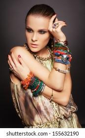 portrait of beautiful young brunette woman in numerous bracelets on dark gray