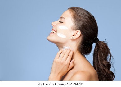 Portrait of a beautiful young brunette woman using skin care product.
