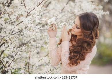 portrait of Beautiful young brunette woman standing near blooming trees in spring garden