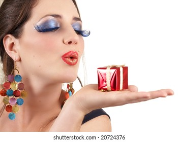 Portrait of a beautiful young brunette woman with dramatic glamour make-up and fashion earrings blowing a little gift box away