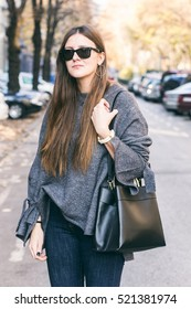 portrait of a beautiful young brunette woman wearing fashionable autumn outfit. fashion blogger posing outdoors in trendy clothing - grey oversized sweater and jeans, holding a trendy black handbag
