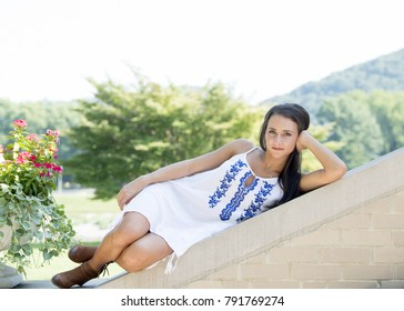 Portrait of a beautiful young brunette woman posing in white short dress as she reclines on wall