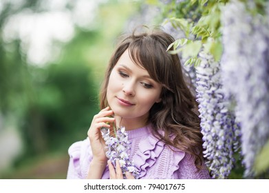 Portrait of a beautiful young brunette woman. A young woman is walking along the spring park. The girl is standing near the wisteria. Blooming park. Spring.