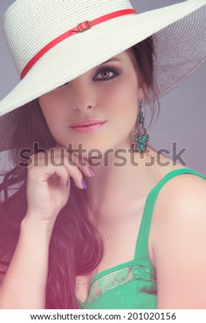a3b82ed9 Portrait of a beautiful young brunette woman. Wearing white hat over long  loose curly hair. Open shoulders summer emerald green dress.