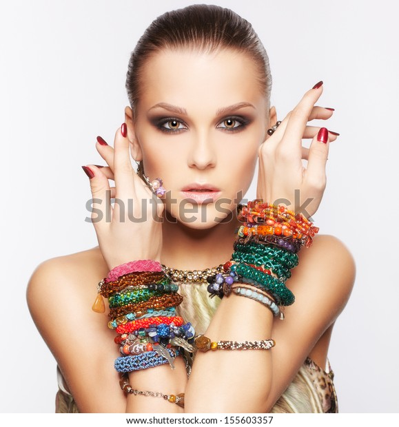 portrait of beautiful young brunette woman posing in multiple bracelets on gray