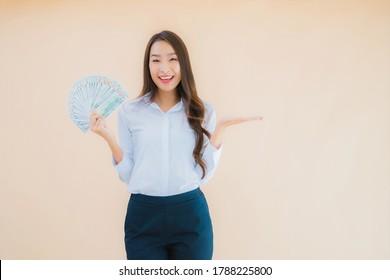 Portrait schöne junge Business-Asiatin-Frau mit Geld oder Geld auf isoliertem Hintergrund