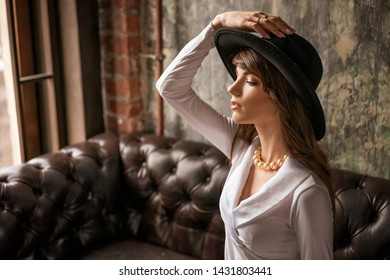 portrait of beautiful young business woman in black hat and white shirt on leather sofa.