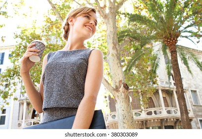 Portrait of a beautiful young business woman commuter walking in classic city, holding a coffee paper cup turning back. Professional businesswoman drinking coffee, on the go lifestyle exterior.