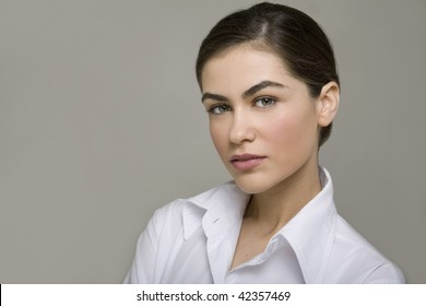 Portrait of a beautiful young business woman smiling against grey background
