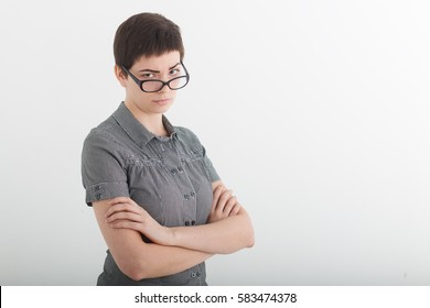 Portrait of beautiful young business woman or angry female teacher accusingly frowning over her glasses