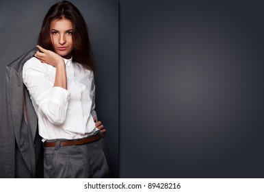 Portrait of a beautiful young business woman standing with hand holding jacket behind her shoulder against grey background and posing fashionable. Looking at camera. Special Copyspace