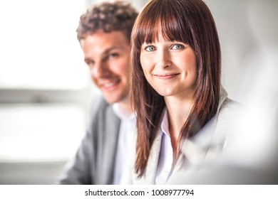 Portrait of beautiful young businesswoman with male colleague in background at office