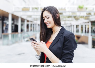 Portrait of a beautiful young businesswoman standing outside using mobile phone