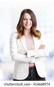 Portrait of beautiful young businesswoman standing at office while looking at camera and smiling.