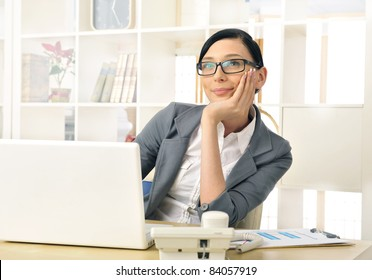Portrait of a beautiful young businesswoman thinking. Office background.