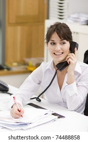 Portrait of a beautiful young businesswoman using phone in office