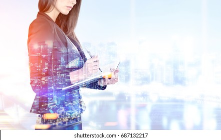 Portrait of a beautiful young businesswoman wearing a black suit and holding a planner and a pen taking notes. Blurred office, night city. Mock up toned image double exposure