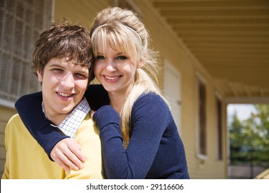 A portrait of a beautiful young caucasian couple outside their house