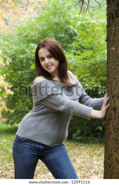 A portrait of a beautiful young caucasian girl leaning against a tree during fall season
