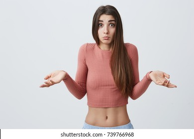 Portrait of beautiful young caucasian student girl with long dark hair in pink top and sport shorts spreading hands, looking n camera with confused expression when stranger on street asks question in