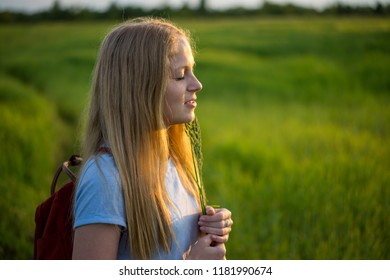 Portrait of beautiful young Caucasian woman with long red hair in plaid shirt and pink tutu tulle skirt,  in park meadow at summer sunset, looking in camera, holding apple