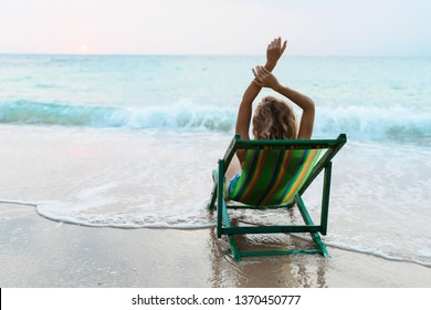 Portrait of beautiful young caucasian woman sitting on sun lounger at beach at sunrise and relaxing. Morning meditation concept