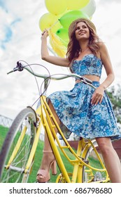 Portrait of a beautiful young caucasian woman on her bike smiling and laughing outdoor. Enjoy summer day, posing on the green lawn. woman in a straw hat holding balloons