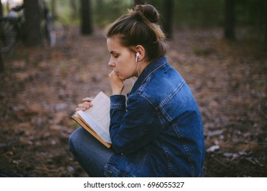 portrait of a beautiful young caucasian woman reading a book outdoor. Sitting on grass