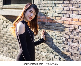 Portrait of beautiful young Chinese woman wearing black tube dress in Shanghai Xintiandi, she smiling on gray brick background, happy time , Asian girl Concept ,Travel Concept.