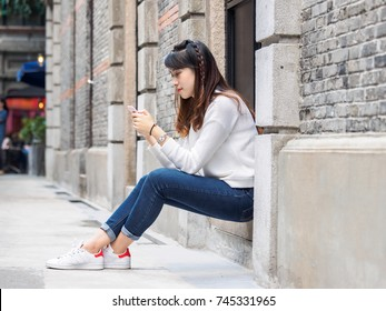 Portrait of beautiful young Chinese woman wearing white sweater and blue jeans sitting at steps and using mobile phone in Shanghai Xintiandi.