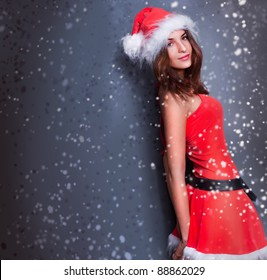 Portrait of beautiful young christmas woman posing wearing santa claus dress. Snowflakes are flying around her